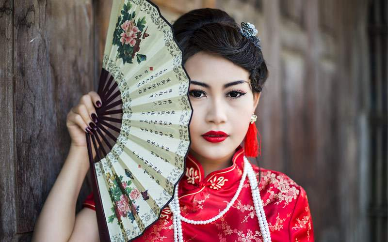 Chinese girl in traditional chinese cheongsam bles