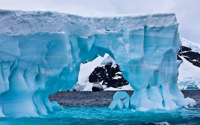 Huge Blue Iceberg with cruise ship in the distance