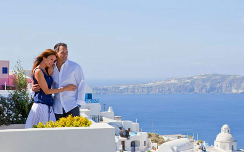 Guests enjoy the view of Greece from a cliff