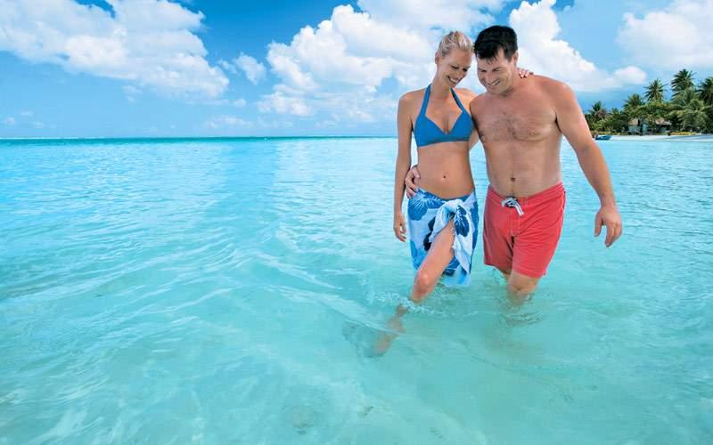 Couple walking through the waters of Motu Tahiti