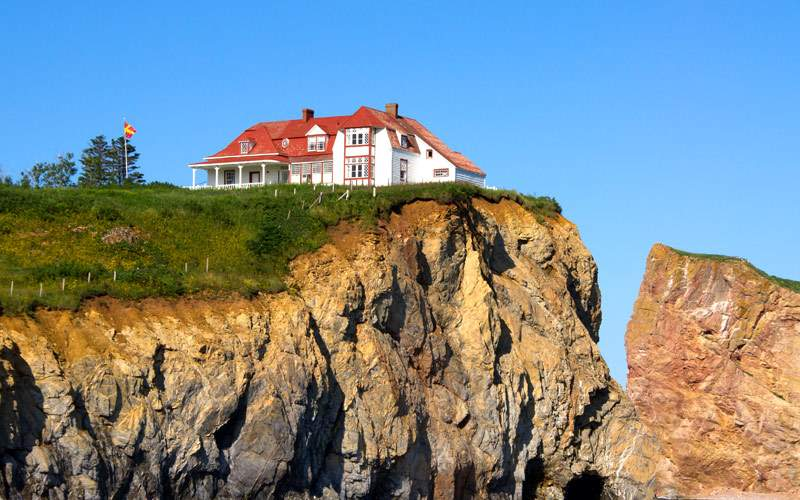 Red house sits on the edge of Percé in Quebec
