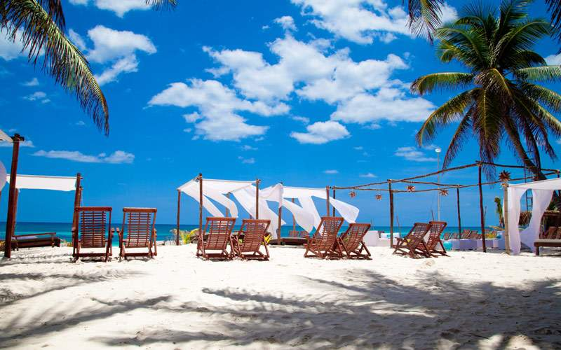 Beach chairs sit at Tulum Beach
