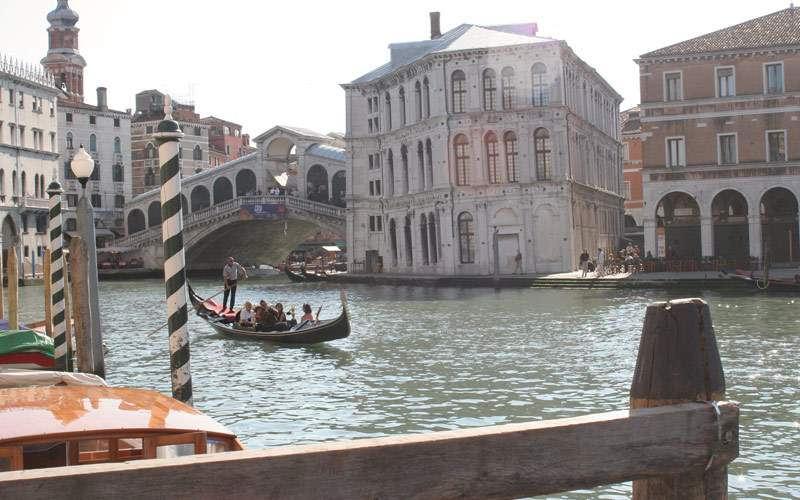 A gondola cruises past the Rialto Bridge in Venice