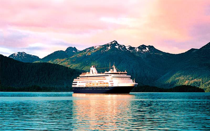 Holland America cruise ship cruises past mountains
