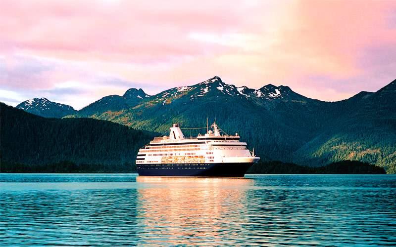 Holland America cruise ship cruises past mountains