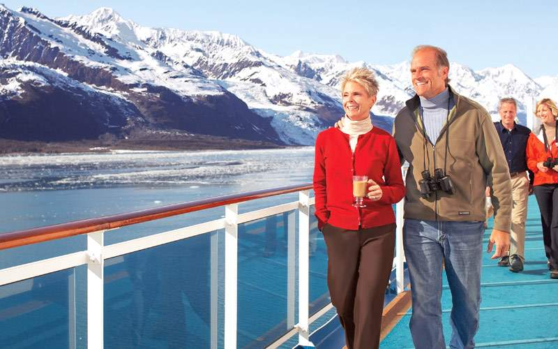 Guests walking as the ship sails past the glaciers