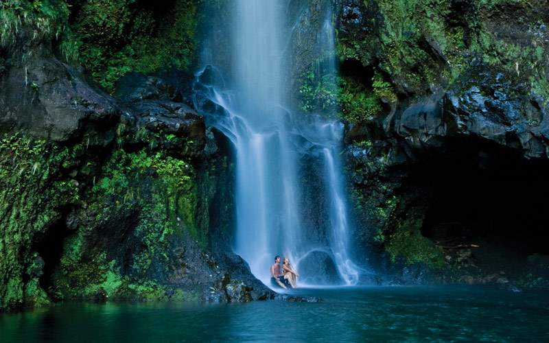 Couple under Hawaiian Waterfall