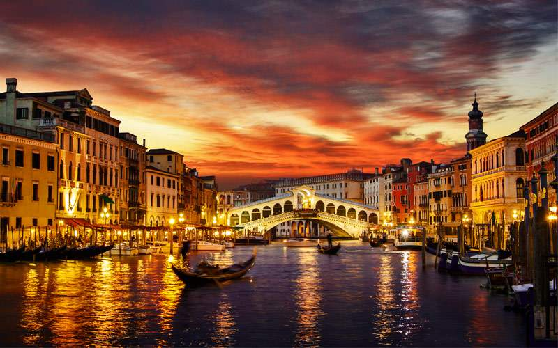 Ponte Rialto and Gondala at sunset in Venice Italy