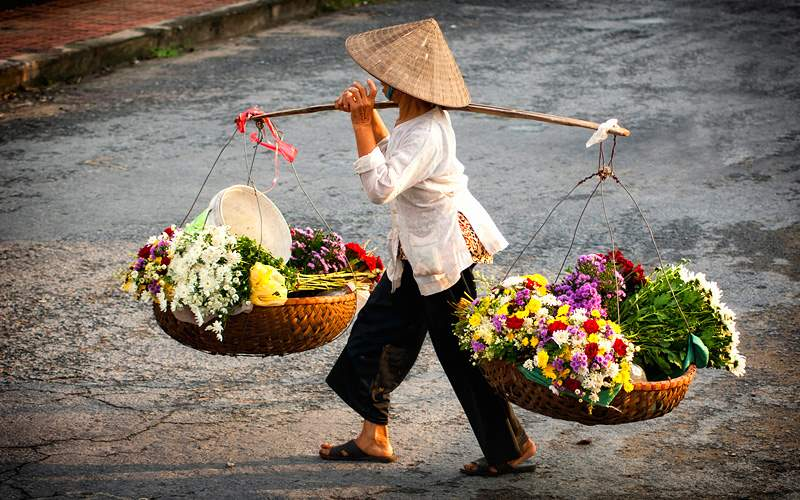 Vietnamese florist vendor at small market in Hanoi