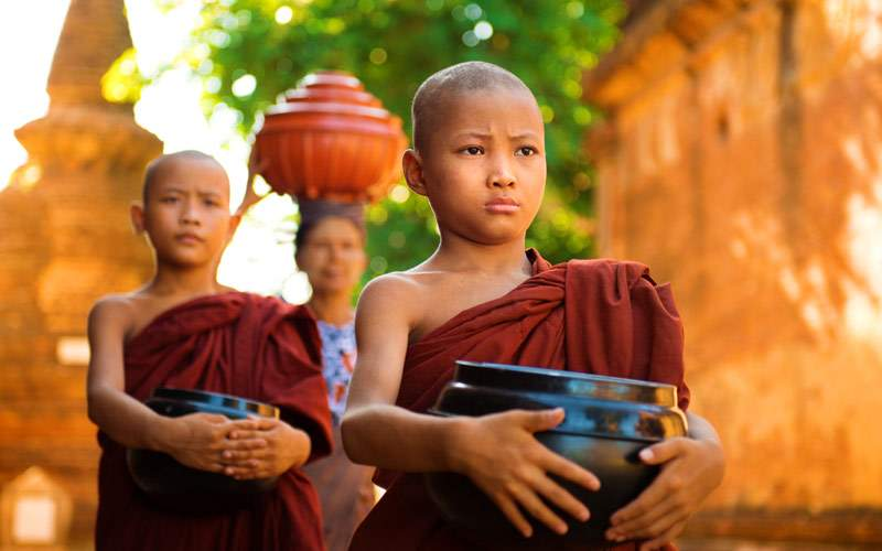 Young Buddhist monks walking morning alms in Bagan