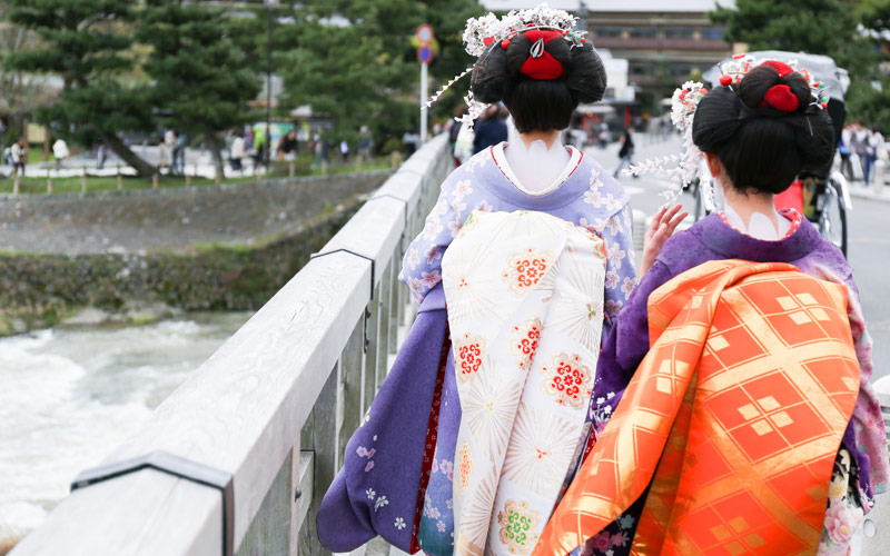 Geisha walking on a bridge in Arashiyama Japan