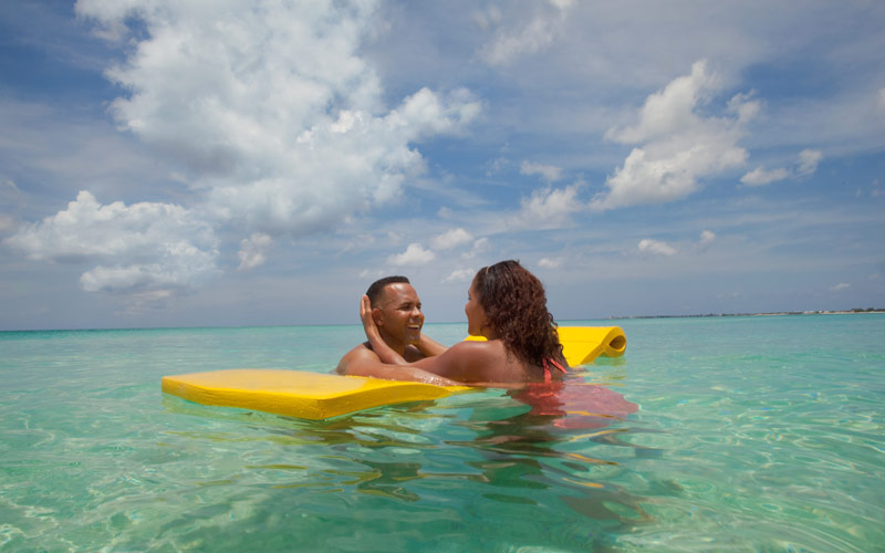 Couple enjoys relaxing on a raft in the Caribbean