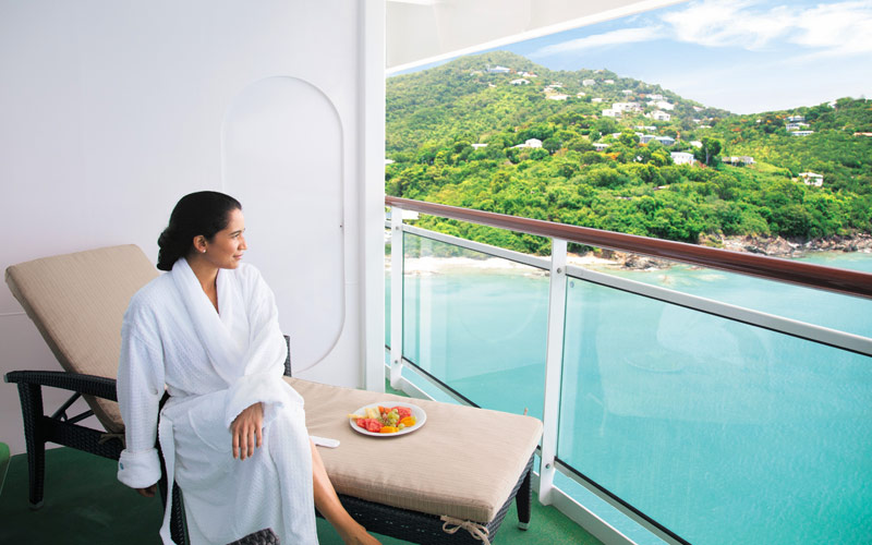 Woman enjoys a spa suite balcony on the Epic