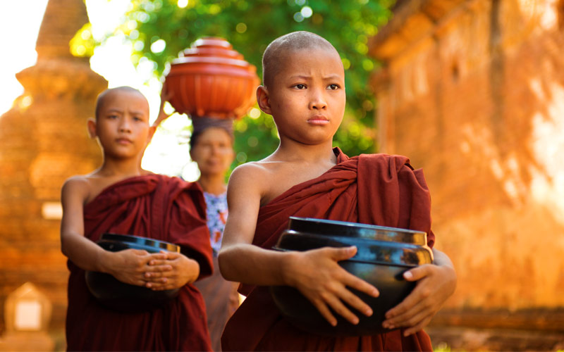 Young Buddhist monks walking morning alms Bagan 02