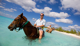 Carnival Cruise Lines men riding horses in the ocean