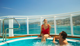Two adults relaxing in a hot tub on Carnival Sunrise