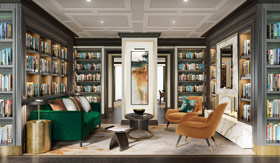 Couch and two chairs surrounded by bookshelves
