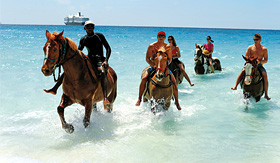 Holland America Line guests riding horses along beach