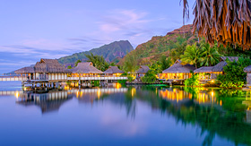 Holland America Line overwater bungalows at dusk French Polynesia