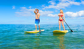 Norwegian Cruise Line couple paddleboarding in tropical waters