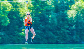 Woman ziplining over river