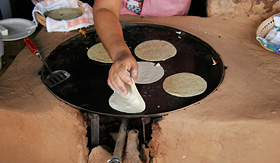 Princess Cruises cooking tortillas in Mexico on a clay and natural gas heated stove oven