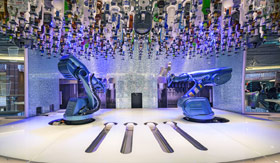 Two robotic arms surrounded by bottles of alcohol and mixers