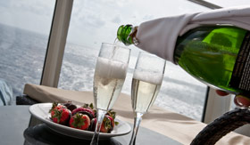 Plate of strawberries and champagne being poured in a glass on balcony