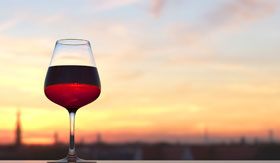 Glass of Red Wine Sitting on Ledge in Sunset
