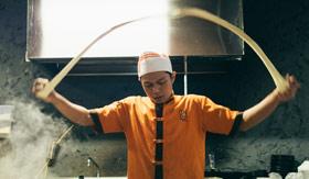 A man tossing noodles