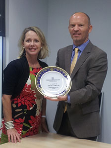 Frans Hansen, President of The Cruise Web, receives a commemorative plate from Tina White, Oceania Cruises' Regional Sales Director