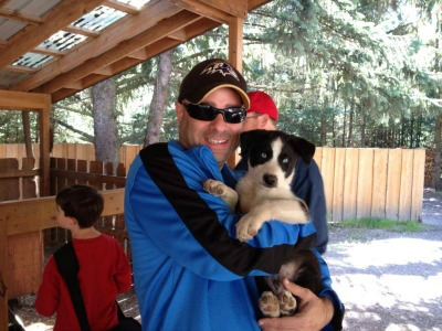 Adam with a husky in Alaska.