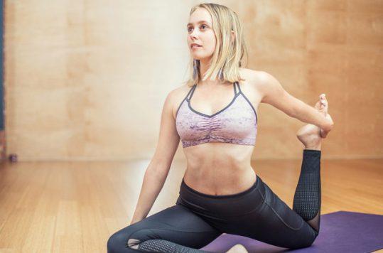 Blonde woman practicing yoga on purple yoga mat in tan yoga studio.