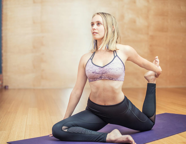 Blonde woman practicing yoga on purple yoga mat in tan yoga studio.