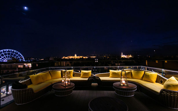 A lounge on the rooftop deck features yellow couches illuminated by the soft light of the port.