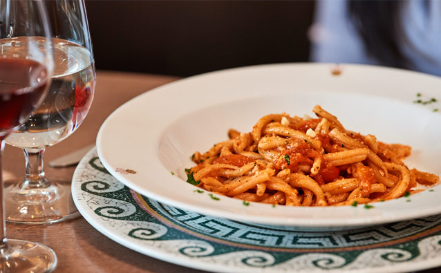 Pasta with tomato sauce in decorative bowl with glass of white wine