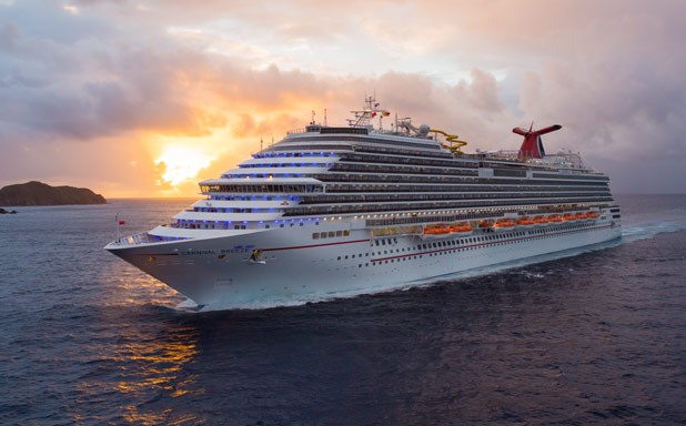 Carnival Breeze sailing through dark blue water at sunset.