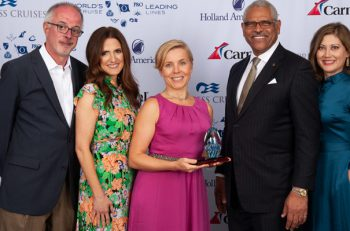Woman in pink address poses with 4 Holland America Line executives with award.