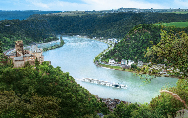 River Beatrice sailing on a European river surrounded y lush scenery and a small town