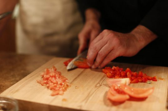 Chef cutting tomato