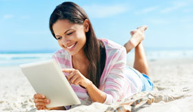 Woman with iPad on beach